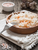 Sauerkraut. Fermented cabbage in a brown clay plate on a wooden table. Healthy vegetarian food and best natural probiotic