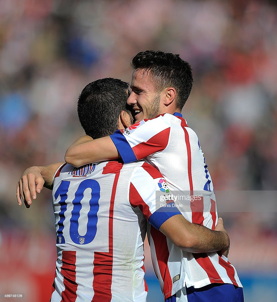 Saul Diges of Club Atletico de Madrid celebrates with Arda Thuran (L) after scoring his team's opening goal during the La Liga match between Club Atletico de Madrid and RC Deportivo La Coruna at Vicente Calderon Stadium on November 30, 2014 in Madrid, Spain.