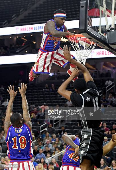 Saul 'Flip' White and Angelo 'Spider' Sharpless of the Harlem Globetrotters toss teammate Jonte 'Too Tall' Hall up for a dunk during an exhibition...