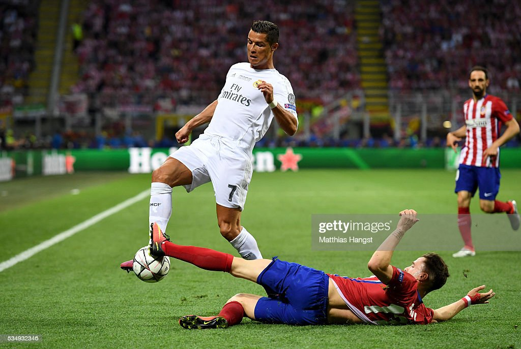 Saul Níguez of Atletico Madrid slides in to tackle <a gi-track='captionPersonalityLinkClicked' href=/galleries/search?phrase=Cristiano+Ronaldo+-+Soccer+Player&family=editorial&specificpeople=162689 ng-click='$event.stopPropagation()'>Cristiano Ronaldo</a> of Real Madrid during the UEFA Champions League Final match between Real Madrid and Club Atletico de Madrid at Stadio Giuseppe Meazza on May 28, 2016 in Milan, Italy.