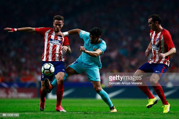 Saul Niguez of Atletico de Madrid and his teammate Diego Godin compete for the ball with Andre Gomes of FC Barcelona during the La Liga match between...