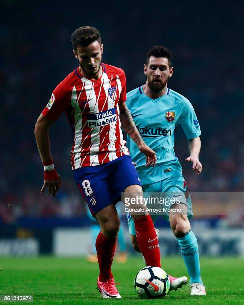 Saul Niguez of Atletico de Madrid competes for the ball with Lionel Messi of FC Barcelona during the La Liga match between Club Atletico Madrid and...