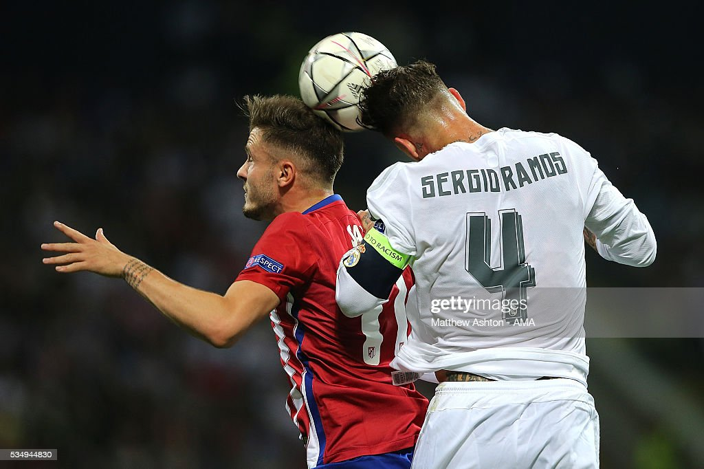 Saul Niguez of Atletico Madrid competes in the air with Sergio Ramos of Real Madrid during the UEFA Champions League final match between Real Madrid and Club Atletico de Madrid at Stadio Giuseppe Meazza on May 28, 2016 in Milan, Italy.