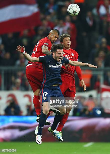Saul Niguez of Atletico Madrid jumps with Arturo Vidal and Thomas Mueller of Bayern Munich during UEFA Champions League semi final second leg match...