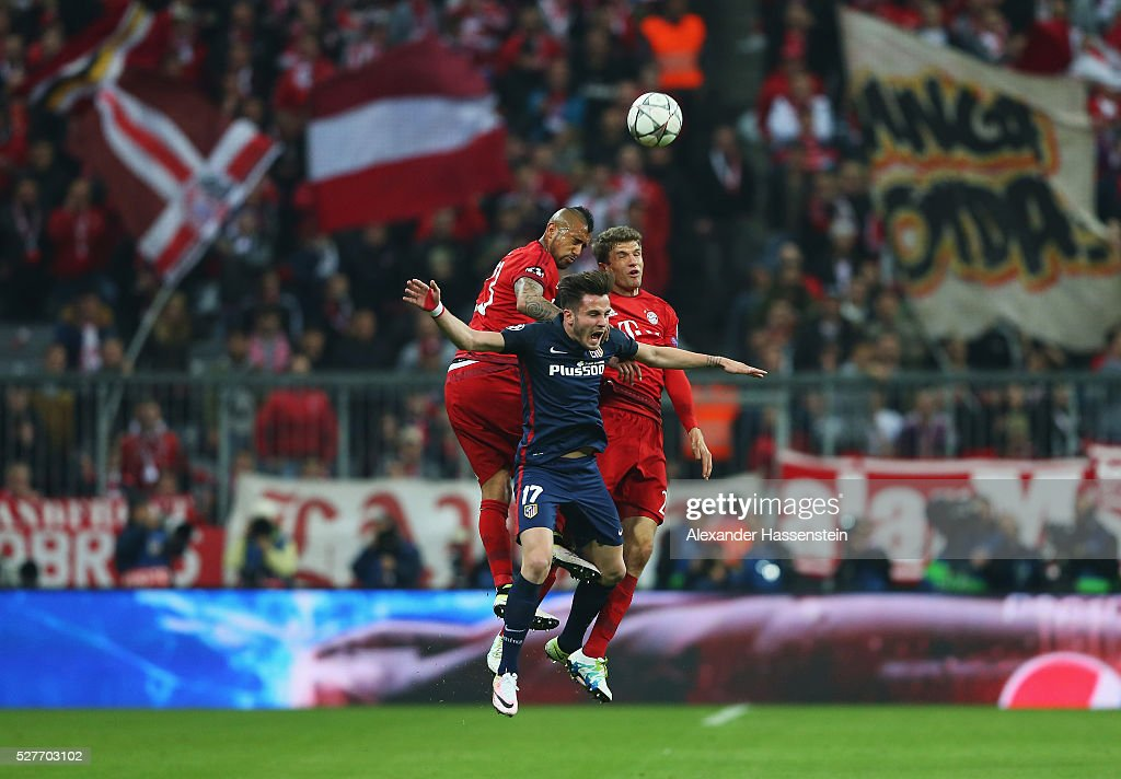 Saul Niguez of Atletico Madrid (17) jumps with Arturo Vidal (L) and Thomas Mueller of Bayern Munich (R) during UEFA Champions League semi final second leg match between FC Bayern Muenchen and Club Atletico de Madrid at Allianz Arena on May 3, 2016 in Munich, Germany.