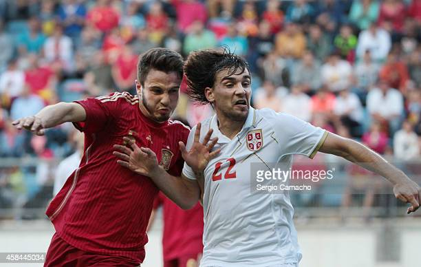 Saul Niguez of Spain duels for the ball with Filip Stojkovic of Serbia the UEFA European Under21 Championship playoff second leg match between Spain...