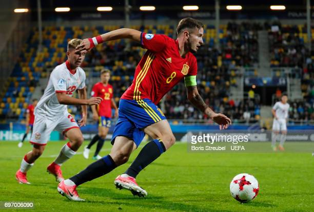 Saul Niguez of Spain is challenged by Nikola Gjorgjev of FYR Macedonia during the UEFA European Under21 Championship match between Spain and...