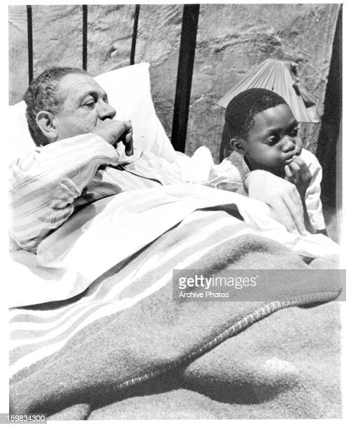 Saul Pelle sitting next to the bed of Sid James in a scene from the film 'Tokoloshe' 1965