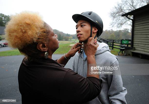 Saundra Adams left assists Chancellor Lee Adams with his riding helmet at Misty Meadows in Weddington NC on November 4 2014 Chancellor is the son of...
