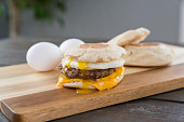 Sausage, egg and cheese breakfast sandwich with english muffin on cutting board with running yoke