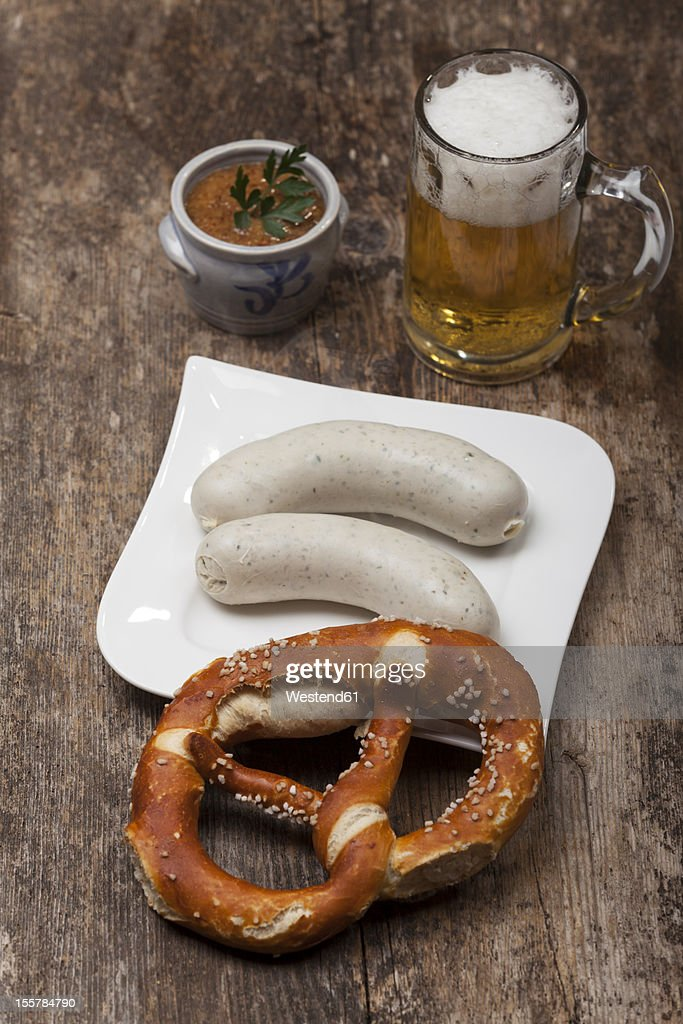 Sausage in plate with preztel and beer mug on table