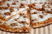 A shot of the pizza slice on a stripy background.