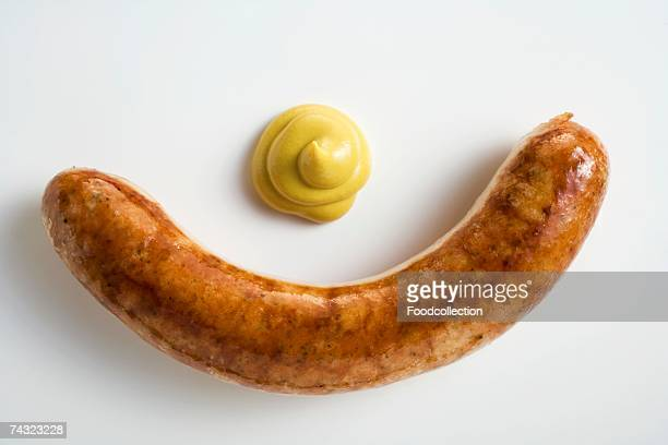 A sausage with mustard on a white background
