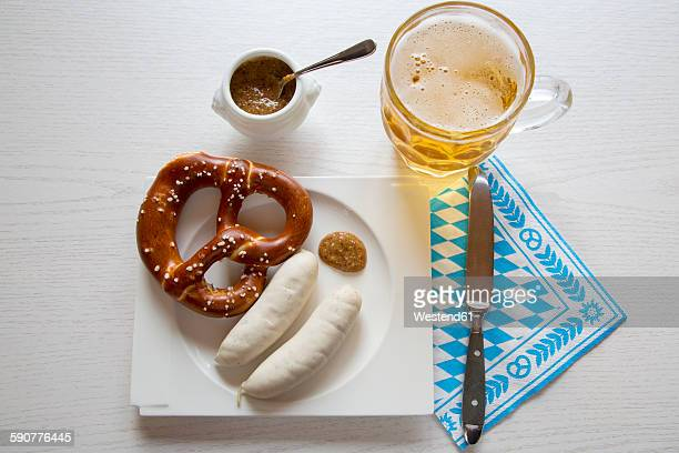Sausage with preztel on plate and beer mug, sweet mustard, knife and napkin