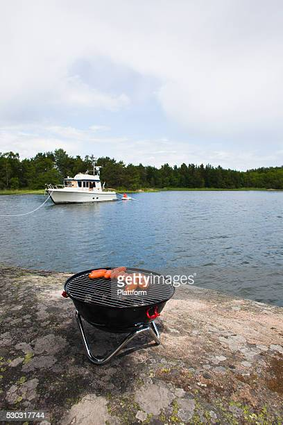 Sausages on barbecue grill on shore