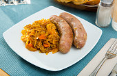 Tasty baked meat sausages with vegetable garnish of braised cabbage