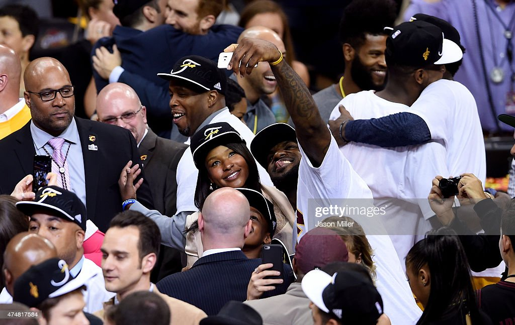 Savannah Brinson and LeBron James of the Cleveland Cavaliers celebrateon the court and take a selfie after defeating the Atlanta Hawks during Game...