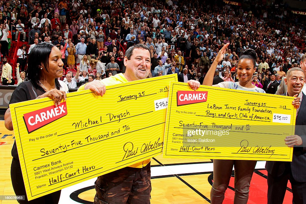 Savannah Brinson, fiancee of LeBron James of the Miami Heat, right, and fan Michael Drysch pose with checks after Drysch made a half-court shot to win $75,000 for himself and $75,000 for the LeBron James Family Foundation Boys and Girls Club of America during halftime of a game against the Detroit Pistons on January 25, 2013 at American Airlines Arena in Miami, Florida.