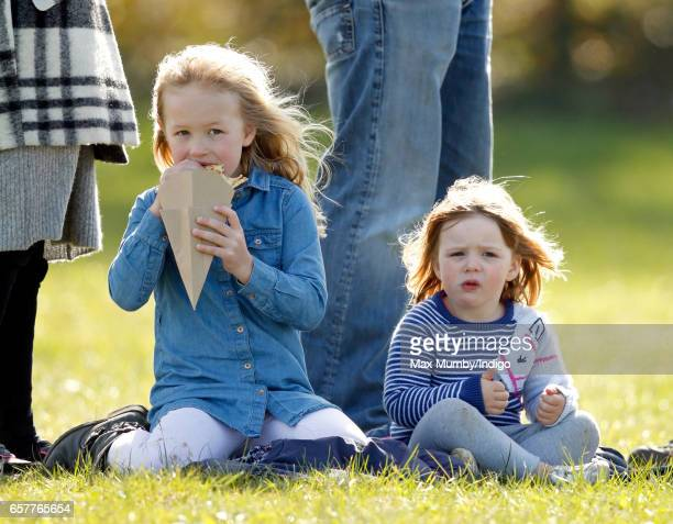 Savannah Phillips and cousin Mia Tindall eat crepes as they attend the Gatcombe Horse Trials at Gatcombe Park on March 25 2017 in Stroud England