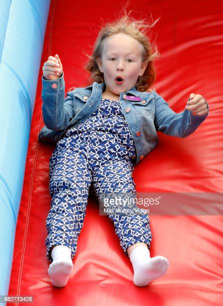 Savannah Phillips plays on an inflatable slide as she accompanied by her parents Peter and Autumn Phillips attends day 4 of the Royal Windsor Horse...