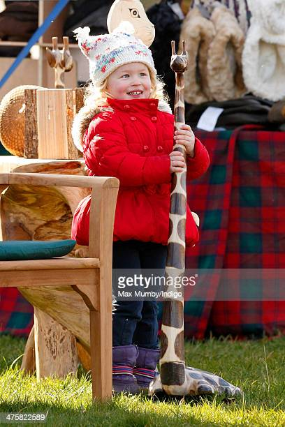 Savannah Phillips plays with a wooden giraffe as she accompanied by her parents Peter and Autumn Phillips attends The Duke of Beaufort's Hunt...