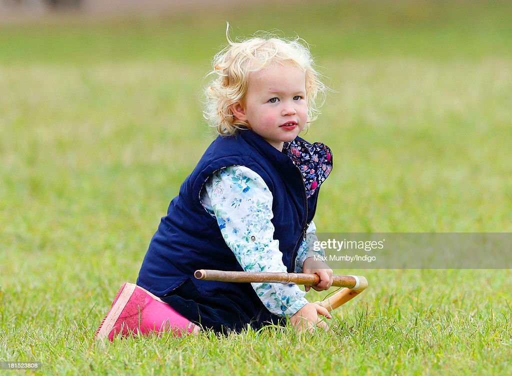 Savannah Phillips plays with her Grandmother's (Princess Anne, The Princess Royal) shepherds crook as she and her parents Peter and Autumn Phillips attend the Gatcombe Horse Trials at Gatcombe Park, Minchinhampton on September 21, 2013 in Stroud, England.