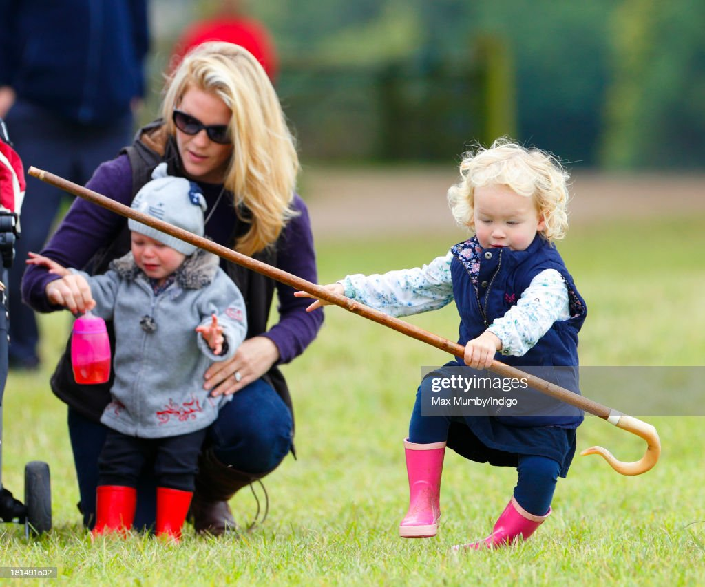 Savannah Phillips (right) takes a tumble whilst playing with her Grandmother's (Princess Anne, The Princess Royal) shepherds crook as her mother Autumn Phillips looks on at the Gatcombe Horse Trials at Gatcombe Park, Minchinhampton on September 21, 2013 in Stroud, England.