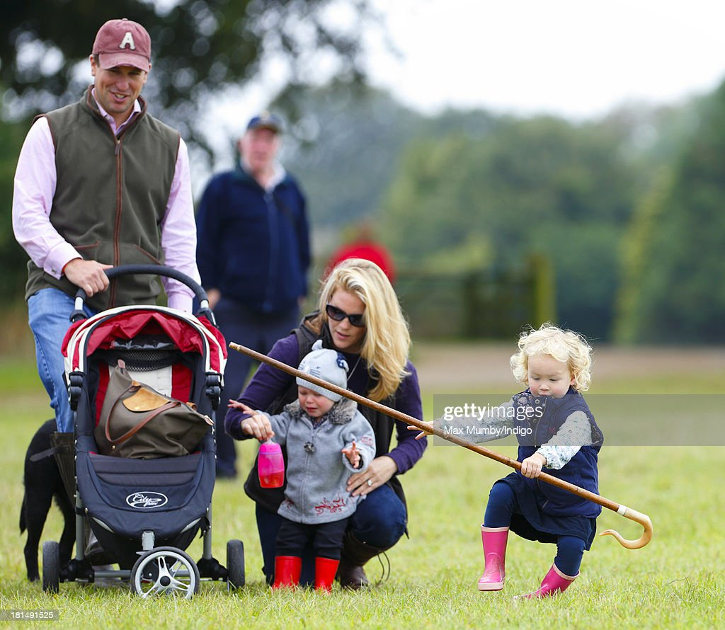 Savannah Phillips (right) takes a tumble whilst playing with her Grandmother's (Princess Anne, The Princess Royal) shepherds crook as her parents Peter Phillips and Autumn Phillips look on at the Gatcombe Horse Trials at Gatcombe Park, Minchinhampton on September 21, 2013 in Stroud, England.