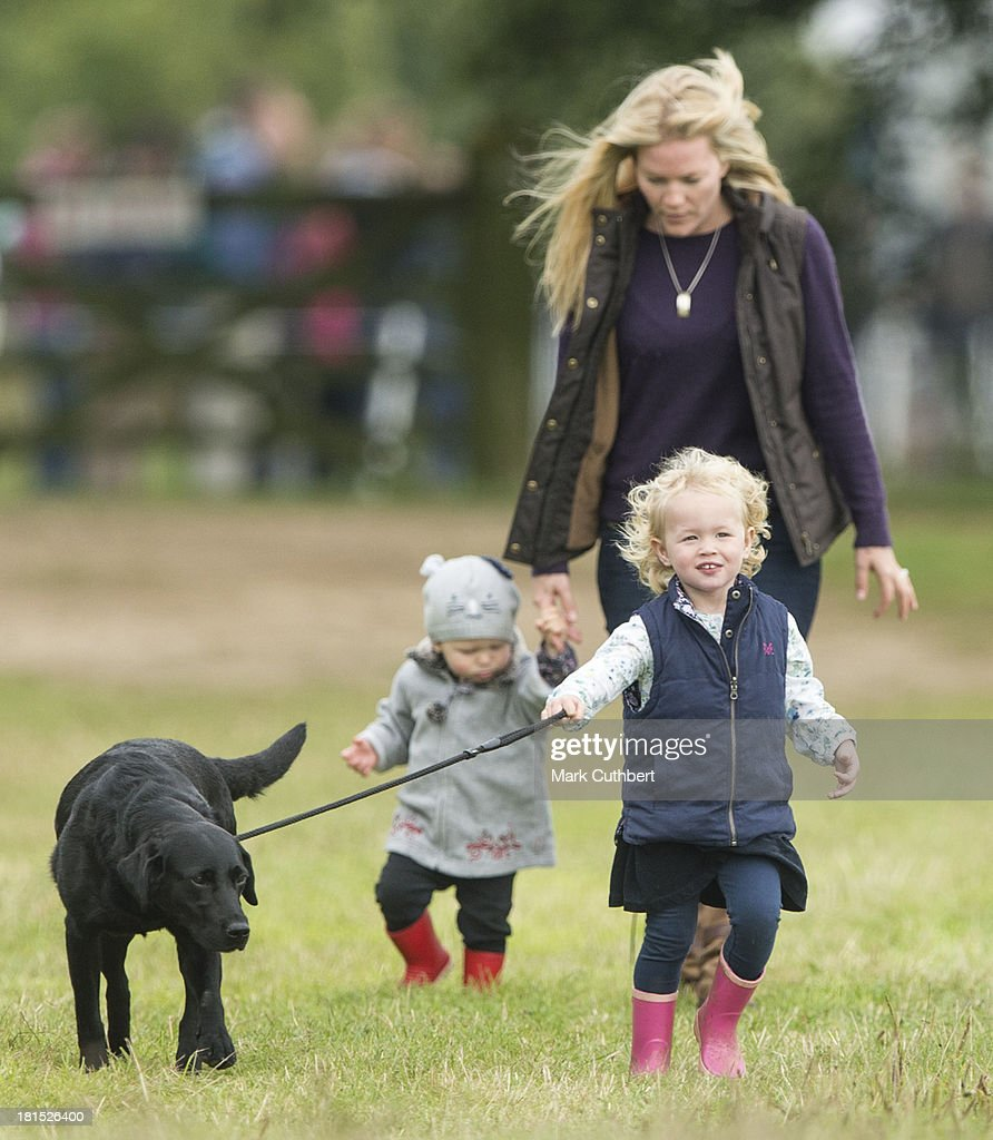 Savannah Phillips walks her dog with Autumn Phillips and Isla Phillips at the Gatcombe Horse Trials at Gatcombe Park on September 21, 2013 in Minchinhampton, England.