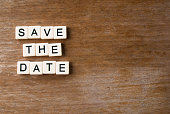 Save the date spelled out on a wooden background.
