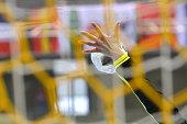 Handball saved by a female handball goalkeeper, seen from behind the net