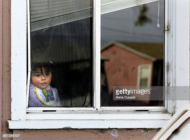 Savelle Beneros age 1 peers out one of the homes for farm workers in south Oxnard along Hueneme Road Another of the homes is reflected in the window...