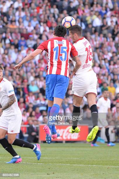 Savic #15 of Atletico de Madrid and Stevan Jovetic #16 of Sevilla FC during The La Liga match between Atletico Madrid v Valencia FC at Vicente...