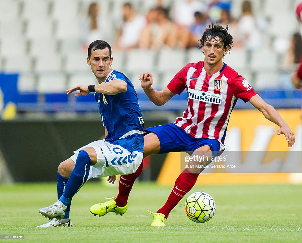 Savic of Club Atletico de Madrid duels for the ball with Miguel Linares of Real Oviedo during a pre season friendly match between Real Oviedo and...