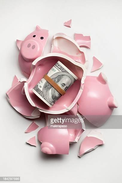 Savings. Broken piggy bank with dollars banknotes