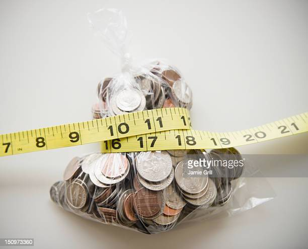 Savings in plastic bag tied up with tape measure