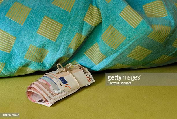 Savings kept under a pillow, roll of cash