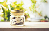 Savings word with money coin in glass jar.For savings and financial investment concept ideas.