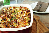 A bread pudding casserole made from French baguette bread, sage breakfast sausage, onions and cheddar cheese