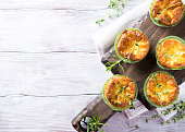 Savory cheddar cheese and leek mini quiches with thyme on dark wooden cutting board. Top view with copy space