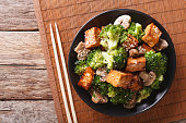 Savory sauteed mixed chinese vegetables with crispy fried tofu on a plate. Horizontal view from above