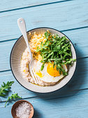 Savoury oatmeal with fried egg, arugula and cheese. Delicious healthy breakfast or lunch. On blue wooden background, top view