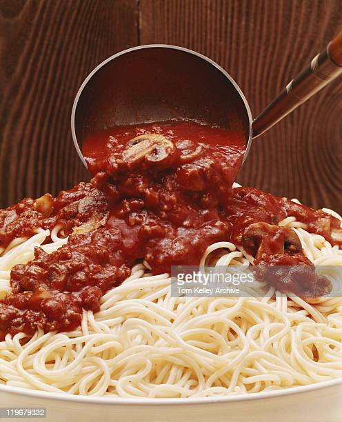 Savoury sauce being poured on spaghetti, close-up