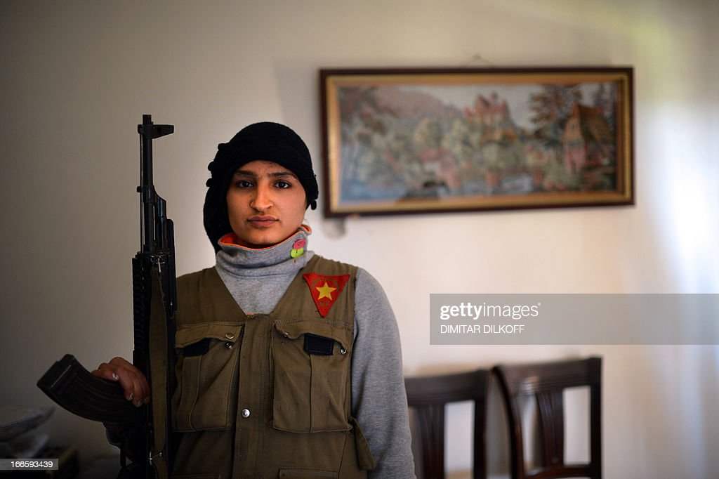 Sawoushka Ahmed, a Kurdish female fighter stands with a gun in the majority-Kurdish Sheikh Maqsud district of the northern Syrian city of Aleppo on April 14, 2013. In northern Syria, the Kurdish population has largely observed a careful compromise with regime and rebel forces, fighting alongside neither, in return for security and semi-autonomy over majority Kurdish areas, but there have been reports in recent weeks of Kurdish fighters joining the battle with Syrian rebels in certain areas, including in Sheikh Maqsud. AFP PHOTO / DIMITAR DILKOFF