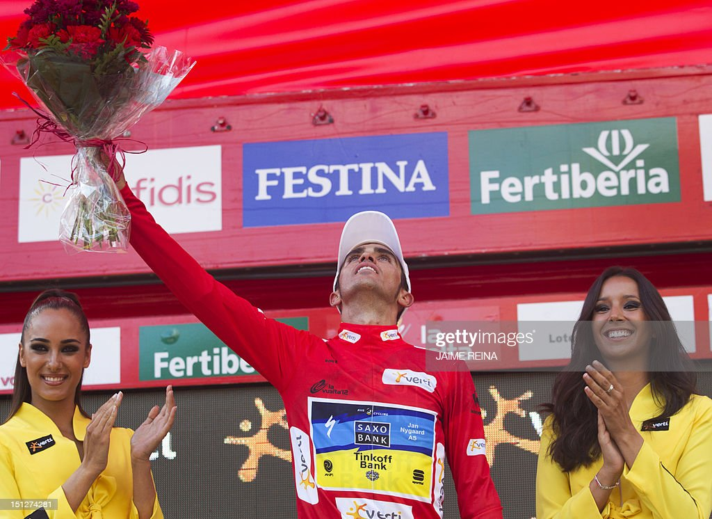 Saxo Bank-Tinkoff Bank Team Spanish cyclist Alberto Contador celebrates with the overall leader's red jersey on the podium of the 17th stage of the Vuelta tour of Spain cycling race, a 187,3 kms ride from Santander to Fuente De, on September 5, 2012. AFP PHOTO/ Jaime REINA