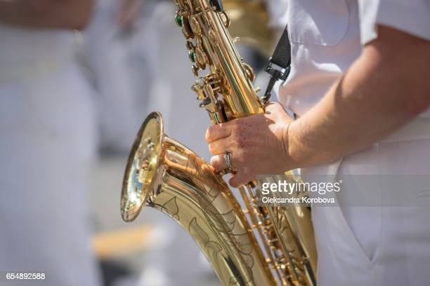 Saxophone player in a military or marching band playing on a sunny day.