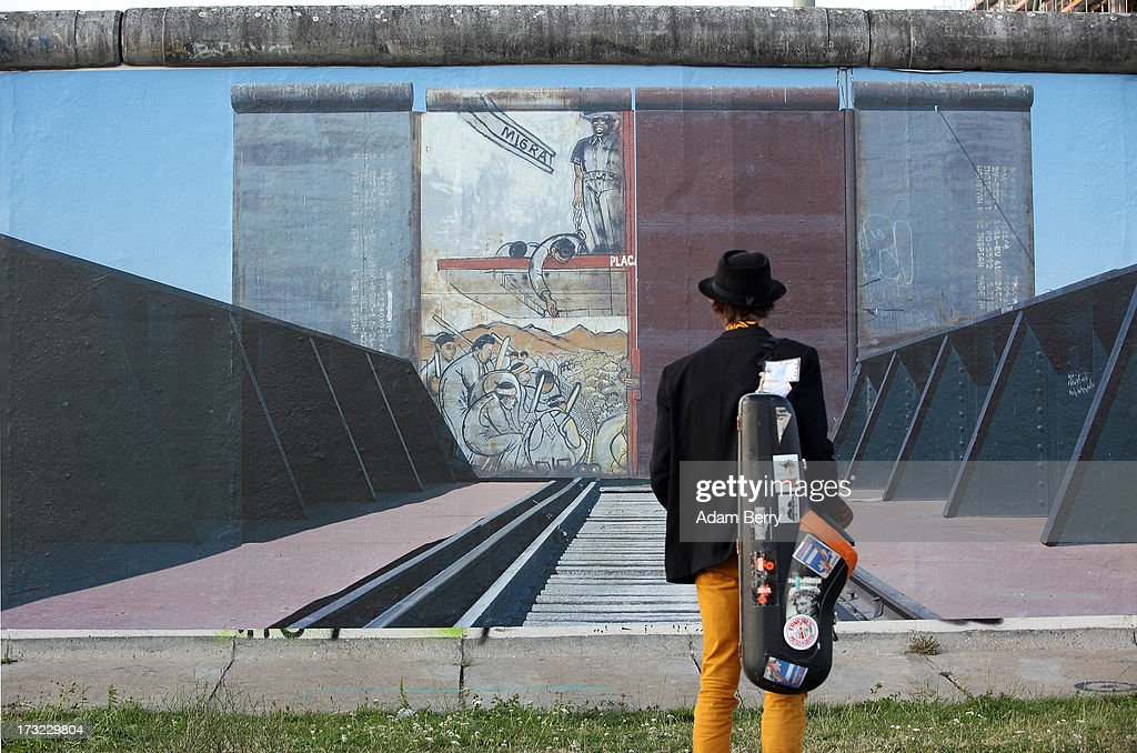 A saxophone player looks at a photo of the United States-Mexico border in Ciudad Juarez, Mexico, hanging as part of the 'Wall on Wall' exhibition at the East Side Gallery section of the former Berlin Wall on July 10, 2013 in Berlin, Germany. A series of photos shot since 2006 by photographer Kai Wiedenhoefer hanging on the Western, river Spree side of the Wall features large pictures of separation barriers in Baghdad, Korea, Cyprus, Mexico, Morocco, Israel, Belfast, and in the former East Germany itself. The opposite side of the stretch of the original Wall is known as East Side Gallery, a memorial to peace and freedom covered in murals questioning the legacy of the original Wall, and the subject of several demonstrations earlier in March this year when sections of it were threatened with removal to make way for a construction site for luxury apartment buildings, discussion of which is still ongoing with a decision expected to be reached in early August.