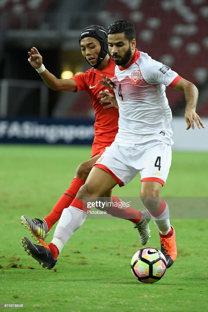 Sayed Dhiya Shubbar of Bahrain (R) runs with the ball against Shawal Anuar of Singapore during the Asian Cup Qualifier match between Singapore and Bahrain at the Singapore Sports Hub on November 14, 2017, in Singapore, Singapore.