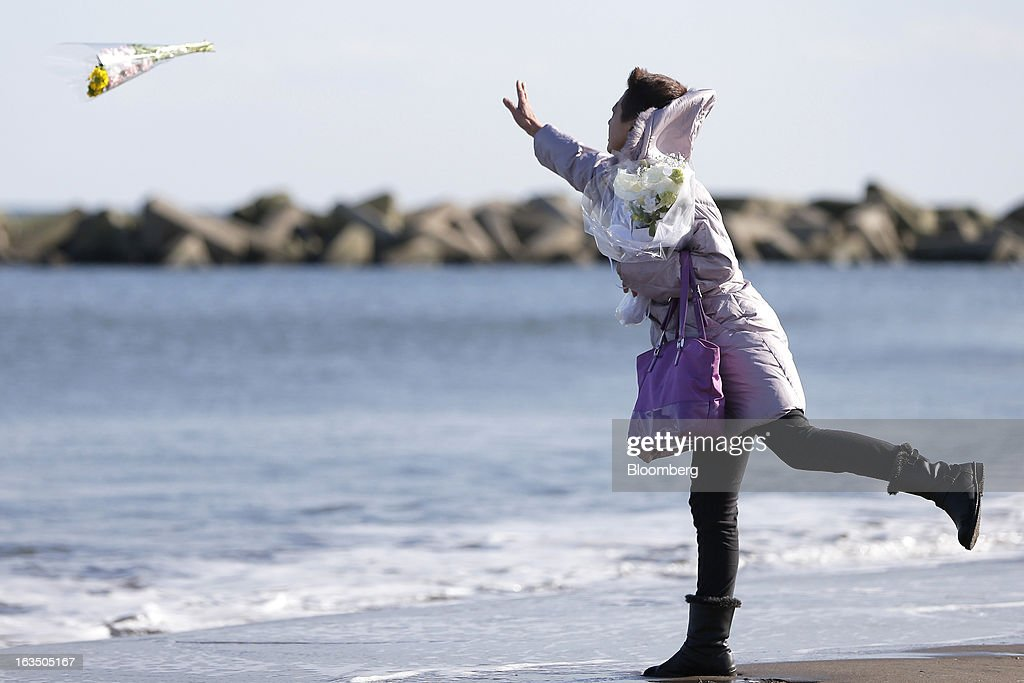 Sayoko Shiroishi throws a bouquet of flowers into the ocean to commemorate her friends who died during the Great East Japan Earthquake and Tsunami on the second anniversary of the event at a coast damaged by the disaster in Sendai, Miyagi Prefecture, Japan, on Monday, March 11, 2013. Two years after a record earthquake devastated Japan's northeast, Prime Minister Shinzo Abe has driven the nation's bond risk to levels from before the disaster with a plan that will add to the world's biggest debt burden. Photographer: Kiyoshi Ota/Bloomberg via Getty Images