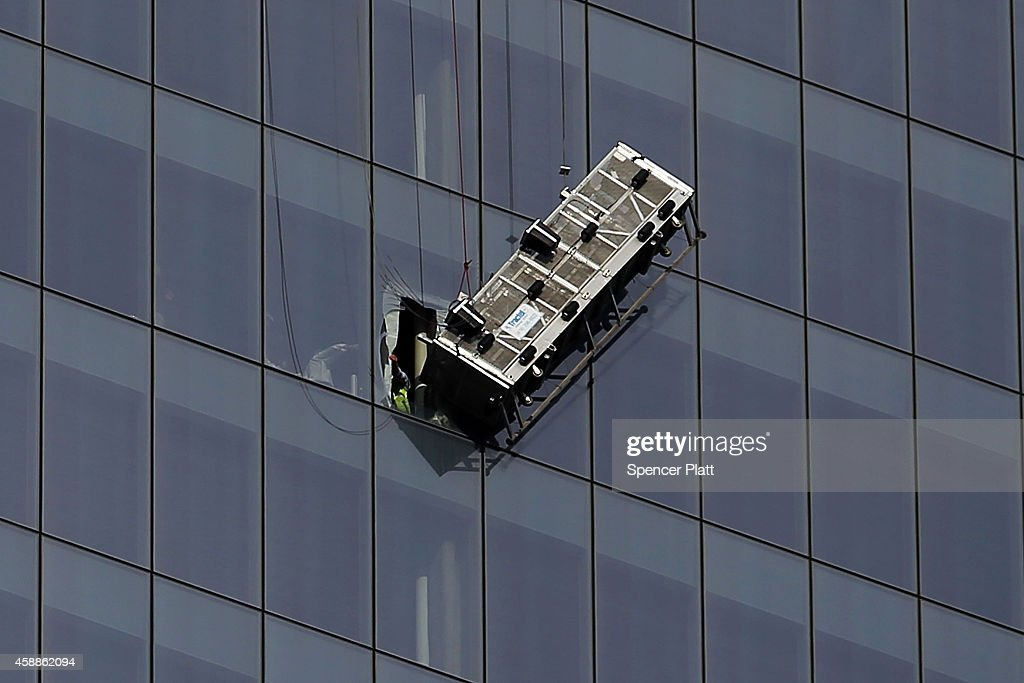 A scaffold that was carrying two workers hangs 69 floors up at One World Trade Center on November 12 2014 in New York City The workers were washing...